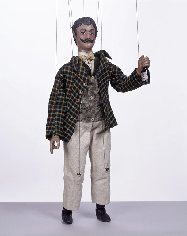 Figure 6: Tiller family marionette company, marionette representing a young 'masher' brandishing a beer bottle, 1870 to 1890, carved wood with paint and fabric, 71 cm, Victoria and Albert Museum.