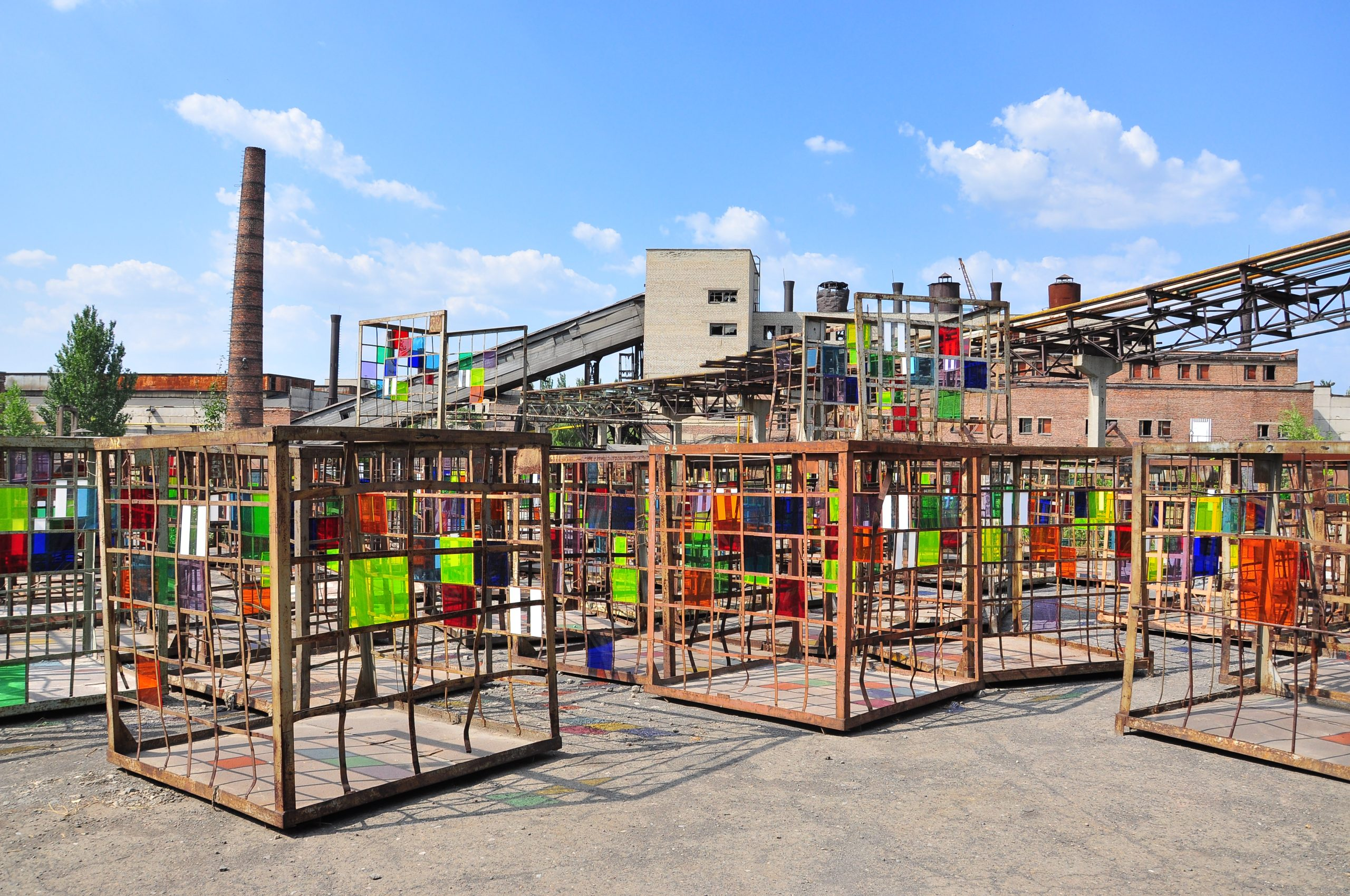 art installation of metal cubes with colored glass plates in the courtyard of a defunct factory