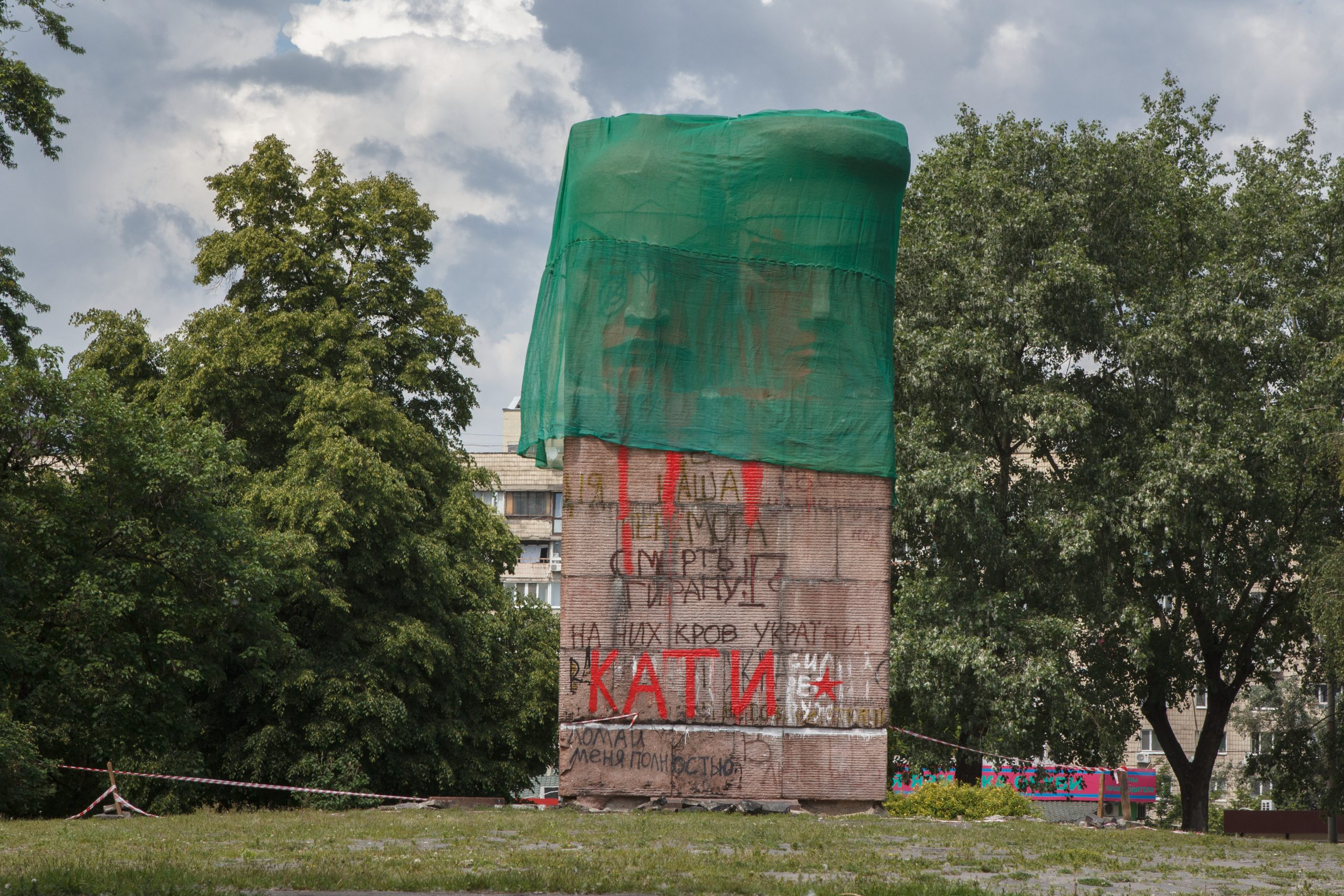 large Soviet World War 2 Red Army monument with graffitti covered by a green cloth in an urban park